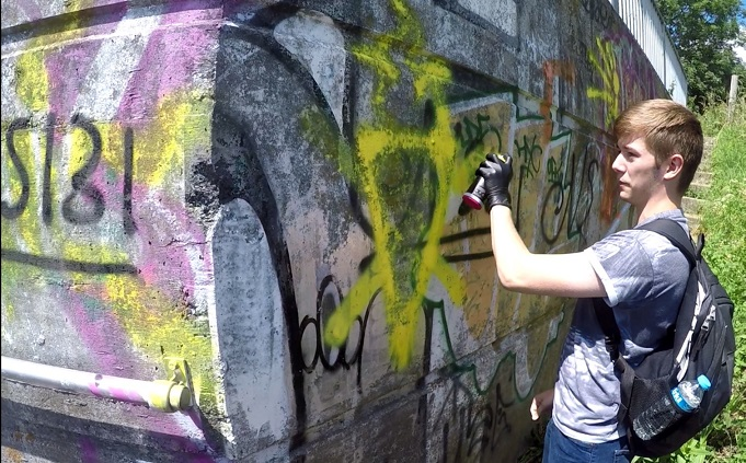Hannam spray-painting a National Action symbol in Swindon in May 2017